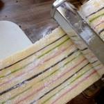 Wer in eine kleine Nudelmaschine investiert, erspart sich das Rollen mit dem Nudelholz.. Die teigplatte mit den aufgebrachten bunten Streifen wird durch die Nudelmaschine gedreht. Dabei entsteht ein buntes Nudelkunstwerk.